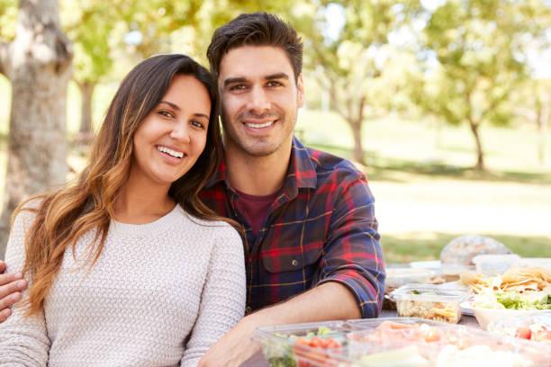 年輕夫婦坐在野餐桌上微笑著拍照 - 異性情侶 個照片及圖片檔