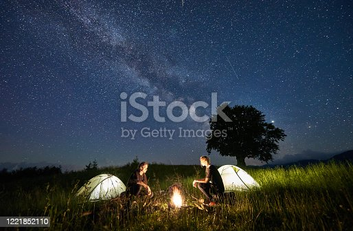Beautiful view of night starry sky over meadow with hikers near illuminated camp tents. Tourists sitting near campfire under magical blue sky with stars. Concept of travelling, hiking and camping.
