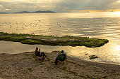 Istanbul, Turkey - November 22, 2020: Young couple sitting by the sea, keeping their social distancing. Relaxing on the beach in quarantine days. Life in the new normal. Mental health, leisure and togetherness.