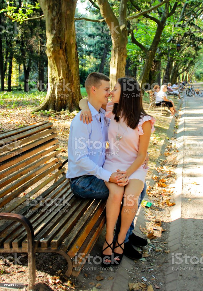 young couple sitting hugs and kissing on a park wooden bench stock