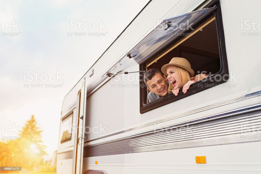 Young couple sitting in a camper van stock photo