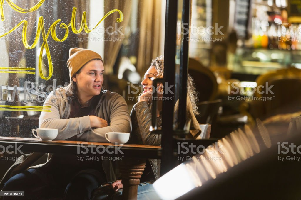 Young couple sitting in coffee shop talking stock photo