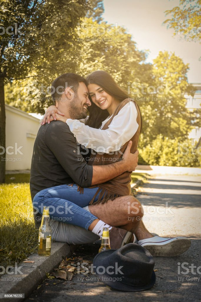 Young Couple Sitting In Park And Holding Bottle Of Drink Girlfriend Sitting On Lap To Her Boyfriend Stock Photo Download Image Now Istock