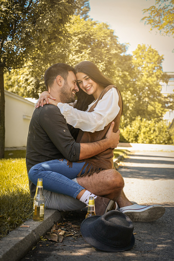 Young Couple Sitting In Park And Holding Bottle Of Drink