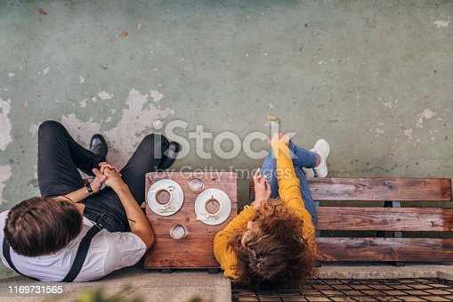 Man and woman, heterosexual couple sitting in a cafe, drinking coffee.