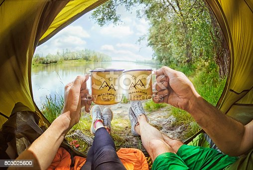 istock Young couple sitting   in the tent and drinking tea while looking on the Desna river , Ukraine 803025600