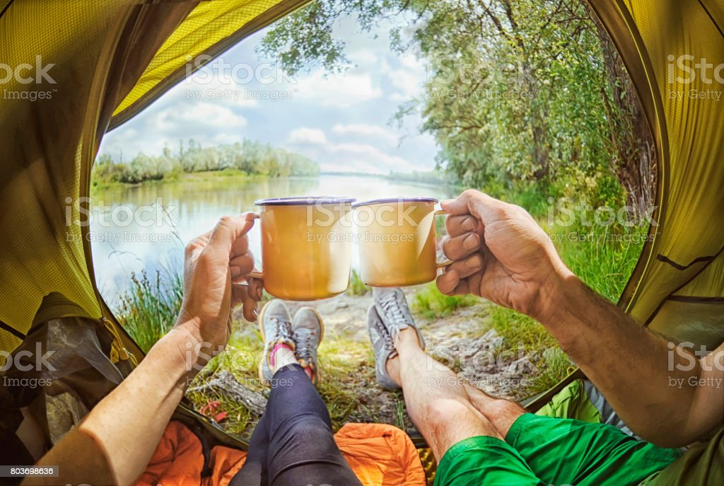 Young couple sitting   in the tent and drinking tea while looking on the Desna river , Ukraine stock photo