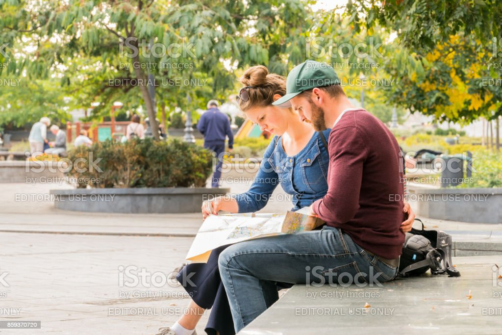 A young couple sitting on a bench looking at a city map in Budapest to find direction. stock photo