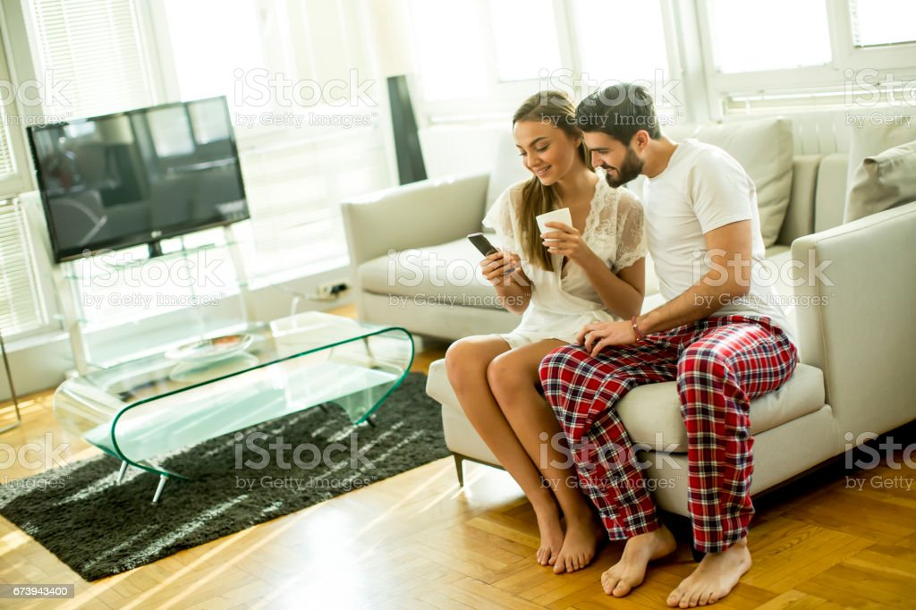 Young couple sitting on a sofa after waking up and looking at the phone, woman drinking coffee foto de stock royalty-free