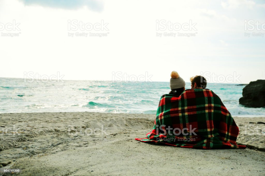 Young couple sitting on beach stock photo