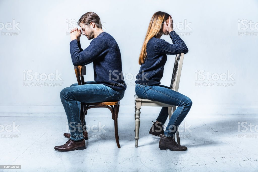 young couple sitting on chairs in opposite directions stock photo
