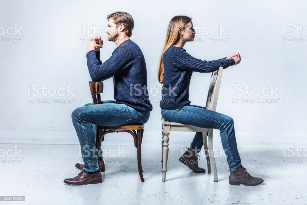 young couple sitting on chairs looking in opposite directions stock photo