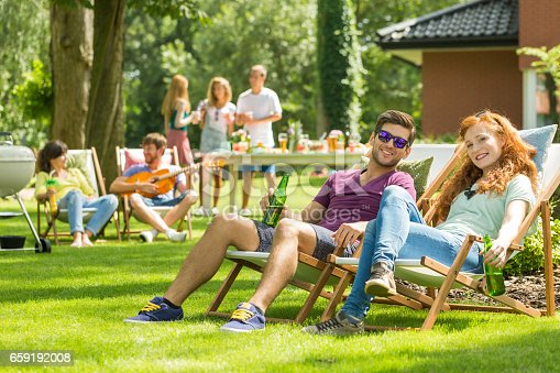 istock Young couple sitting on deckchairs 659192008