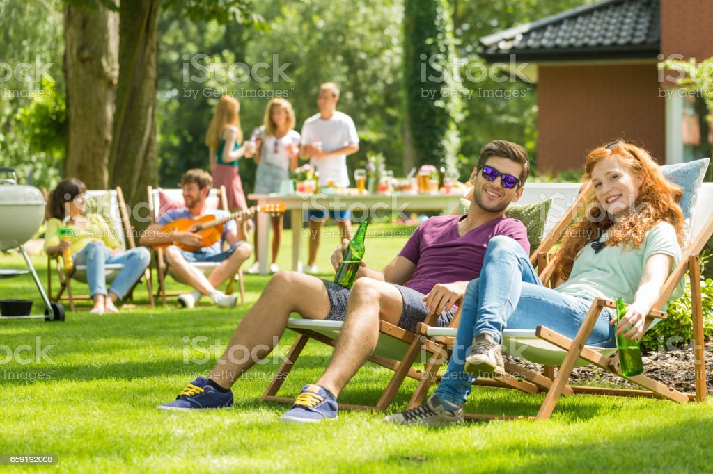 Young couple sitting on deckchairs - foto de stock
