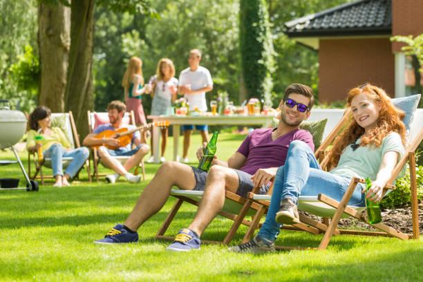 young couple sitting on deckchairs - grillen garten stock-fotos und bilder