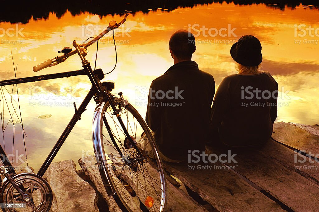 Young Couple Sitting on Dock Watching Sunset royalty-free stock photo