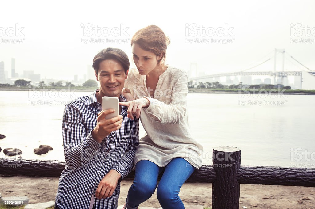 Young couple sitting on fence and using phone royalty-free stock photo