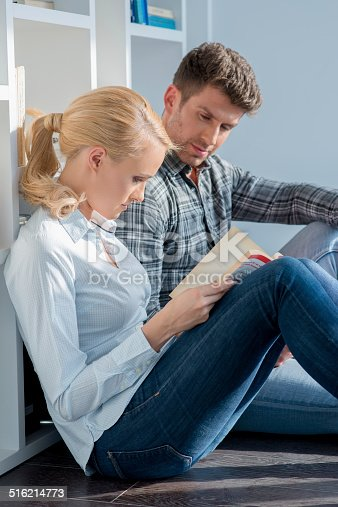 834814926 istock photo Young Couple Sitting on Floor Reading Book 516214773