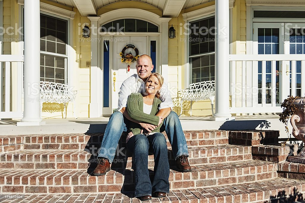 Young Couple Sitting on Front Steps of Their Home royalty-free stock photo