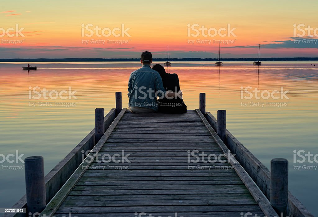 Young couple sitting on jetty at dusk stock photo
