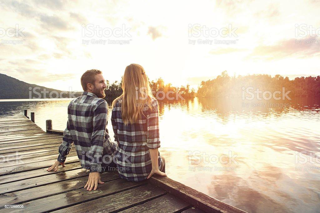Young couple sitting on lake pier enjoying sunset – Foto