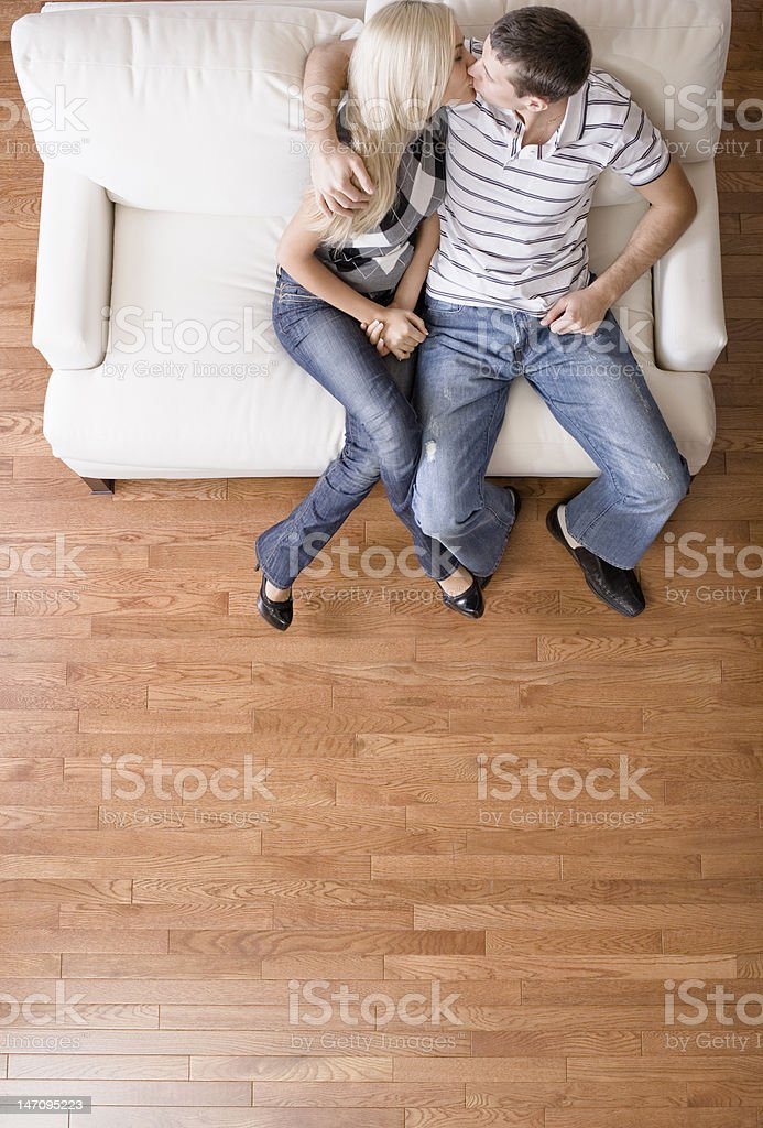 Young Couple Sitting on Love Seat Kissing royalty-free stock photo
