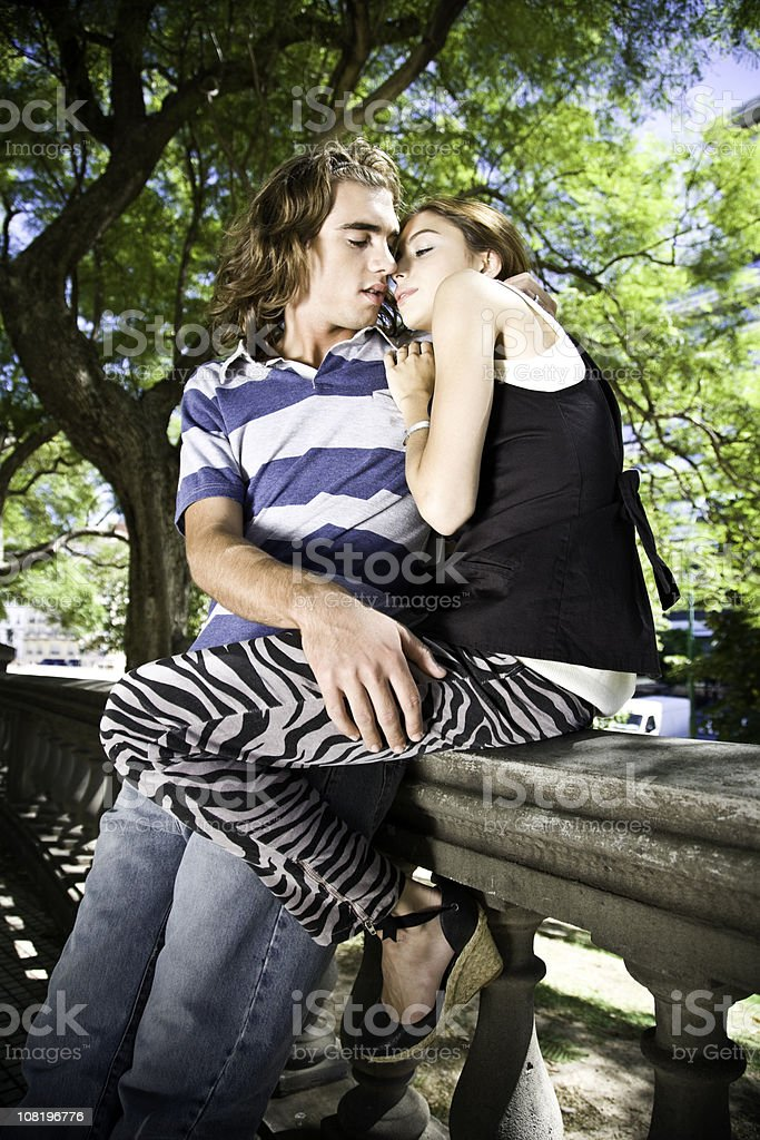 Young Couple Sitting on Park Ledge About to Kiss royalty-free stock photo