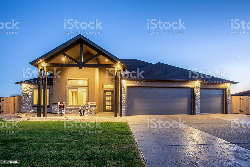 Young Couple Sitting on Porch of New Home at Twilight stock photo