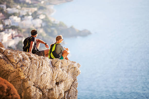 Young couple sitting on rock and enjoying beautiful view stock photo