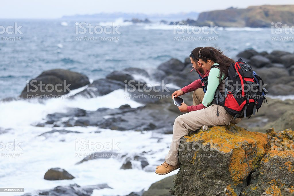 Young couple sitting on rock and holding a digital tablet - foto de acervo