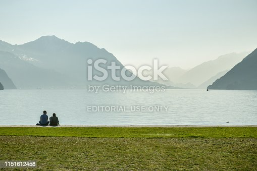 Brunnen, Switzerland - March 30, 2019: Young couple sitting on shores of Lake Luzern in small park in Brunnen, Switzerland during first warm day in spring 2019