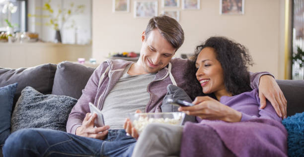 Young couple sitting on sofa and using mobile phone stock photo
