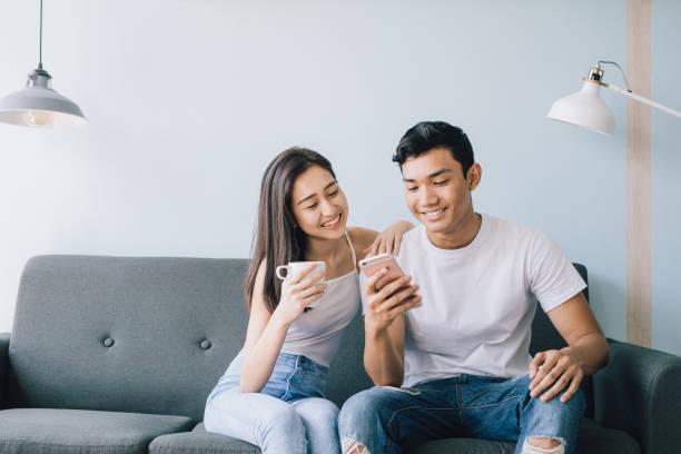 young couple sitting on sofa smiling - divano procrastinazione foto e immagini stock