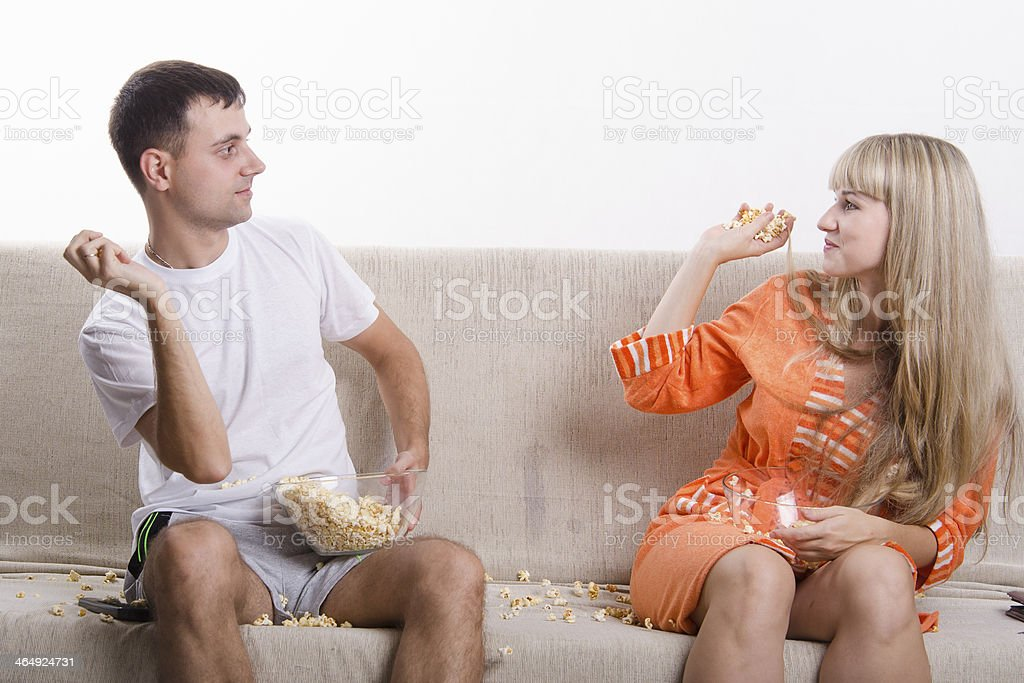 Young couple sitting on the couch,  threw each other popcorn royalty-free stock photo