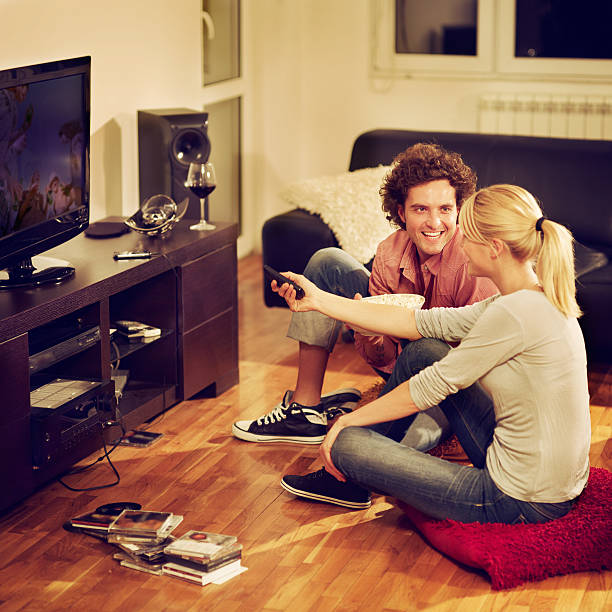 young couple sitting on the floor and watching TV stock photo