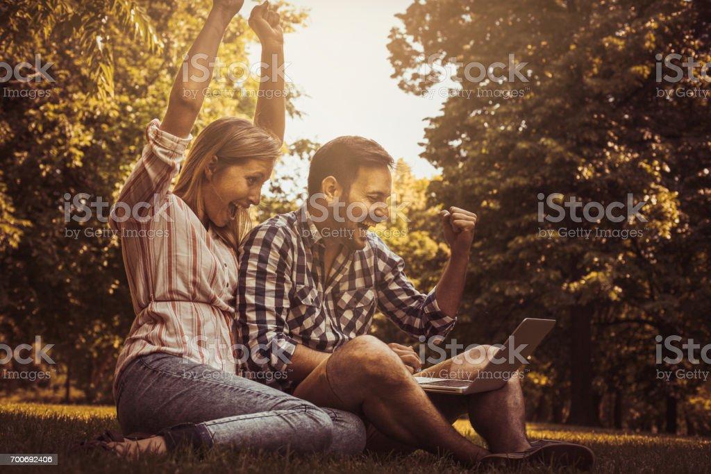 Pareja de jóvenes sentados sobre la hierba. Pareja feliz usando laptop. - foto de stock