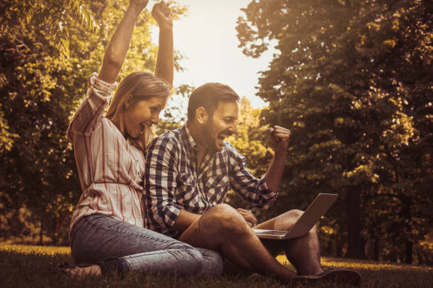 Young couple sitting  on the grass. Happy couple using laptop. stock photo