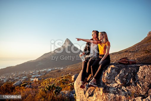 Young couple enjoying a sunny day in nature. They are sitting on the mountain peak and waiting for sunset