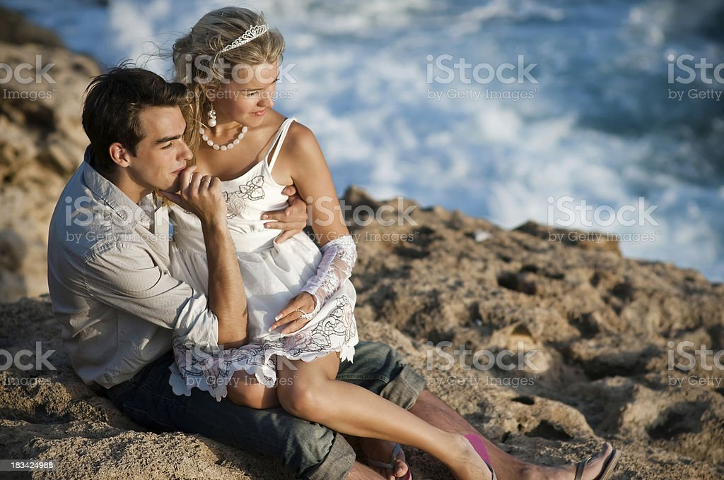 Young couple sitting on the sea shore stock photo