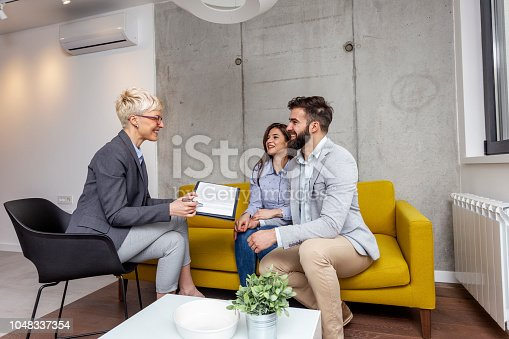 istock Young couple sitting on the sofa in office with real estate agent who holding contract for new home 1048337354