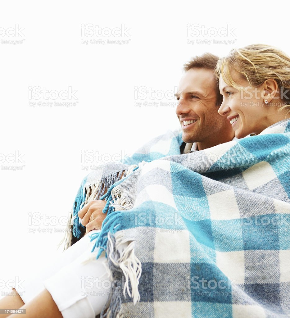 Young couple sitting together covering with shawl and smiling royalty-free stock photo