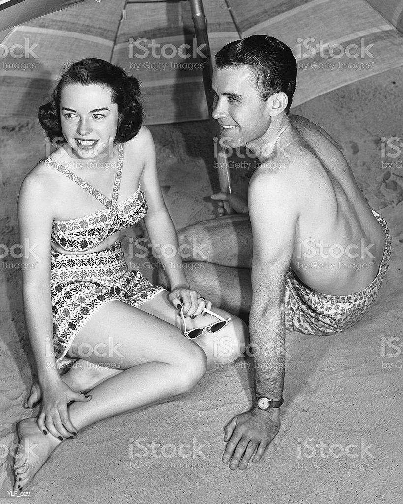 Young couple sitting under beach umbrella royalty free stockfoto