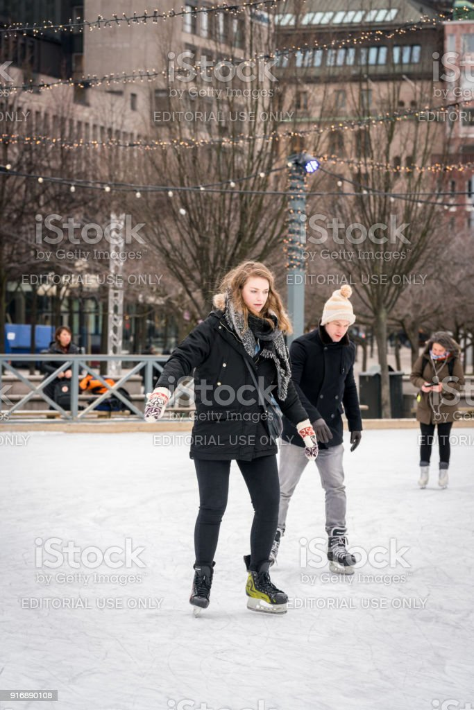 Young couple skating at a public ice skating rink outdoors in the city. royalty-free stock photo