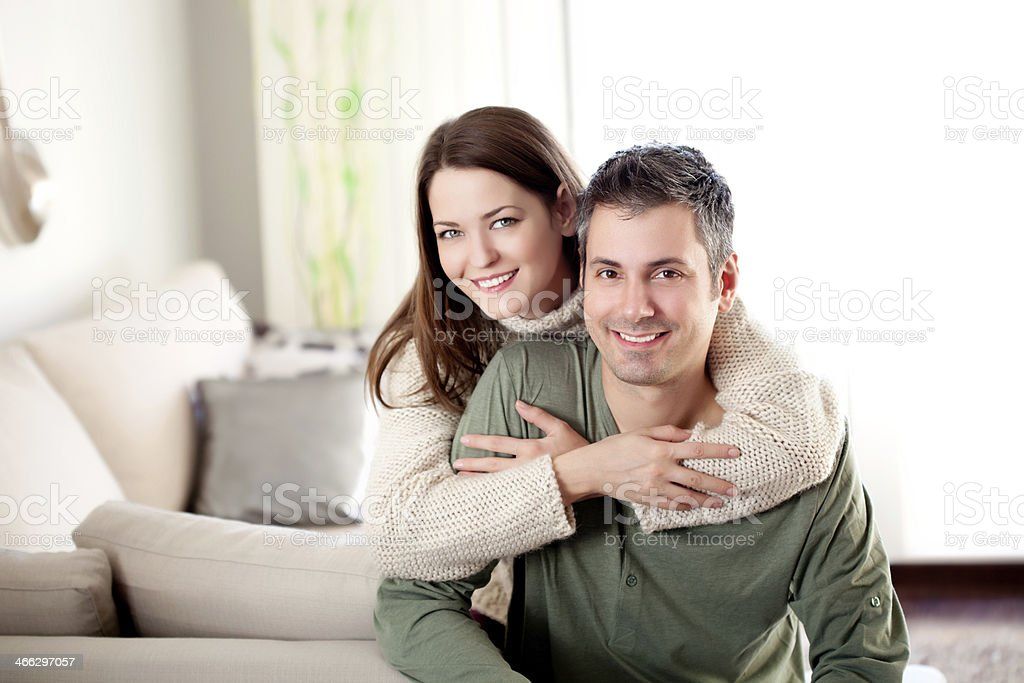 Young couple smiling in living room stock photo