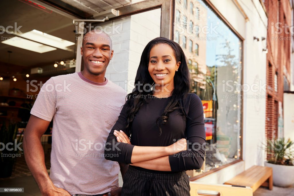 Young couple smiling to camera outside their clothes shop stock photo