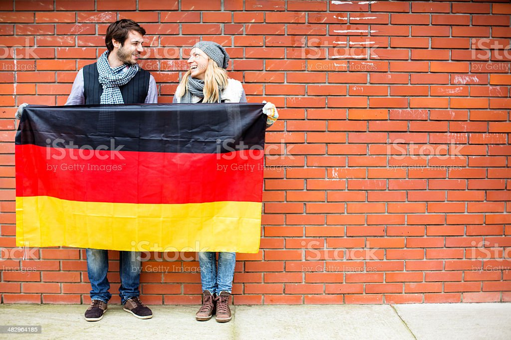Young couple smiling under the German flag royalty-free stock photo