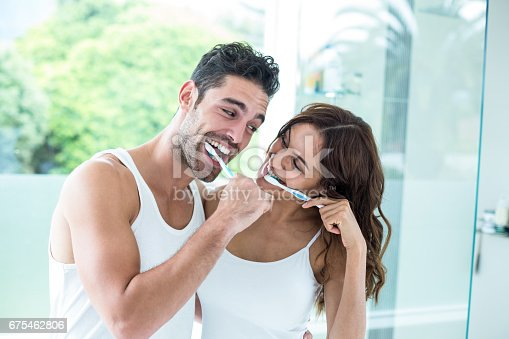 675462768istockphoto Young couple smiling while brushing teeth 675462806