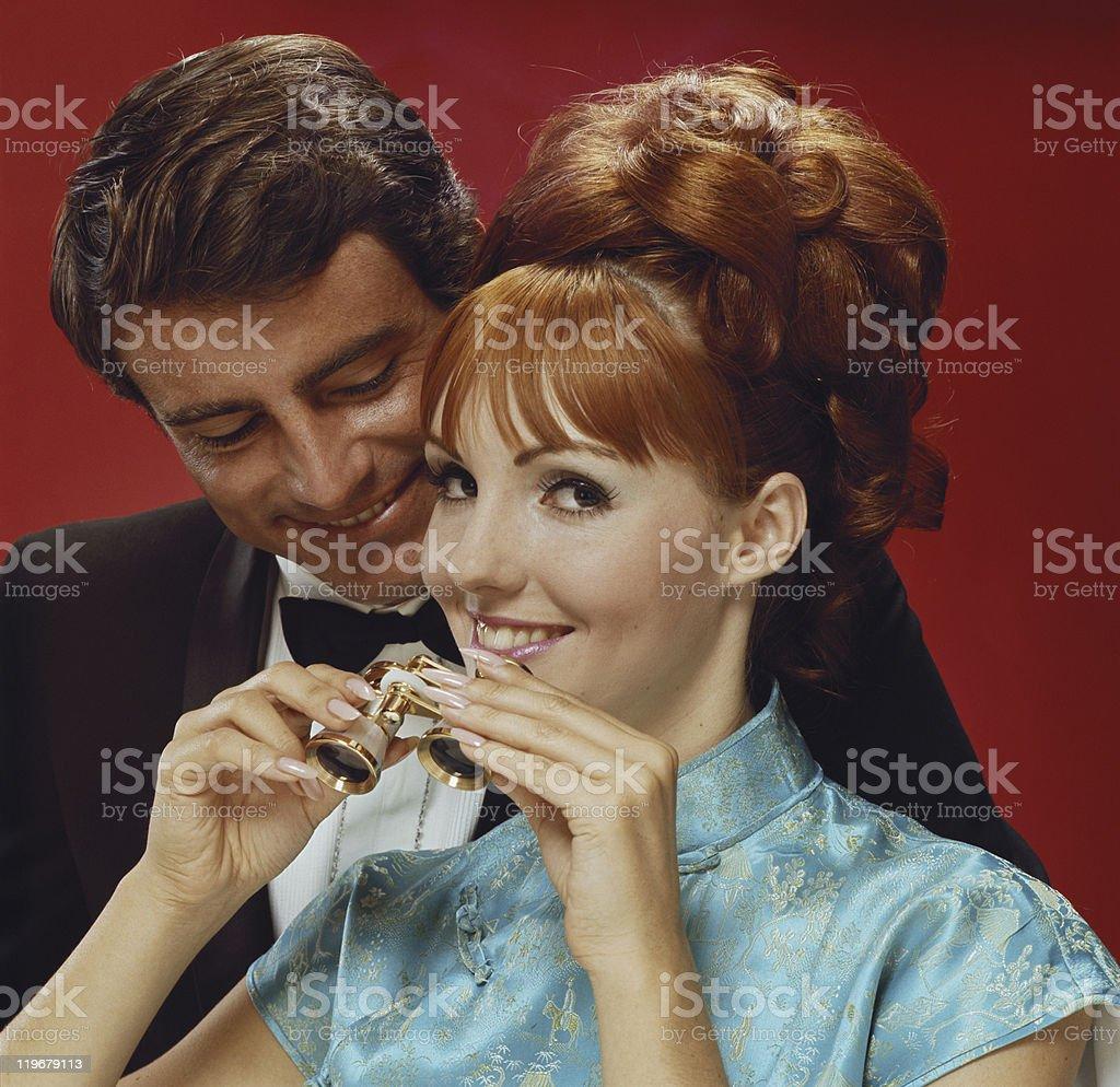 Young couple smiling, woman holding binoculars stock photo
