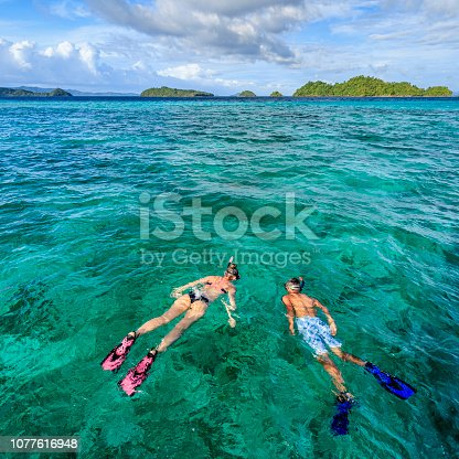 Young caucasian woman with her boyfriend snorkeling and watching turtles, East China Sea, Palawan Island, East China Sea, Philippines, Southeast Asia.