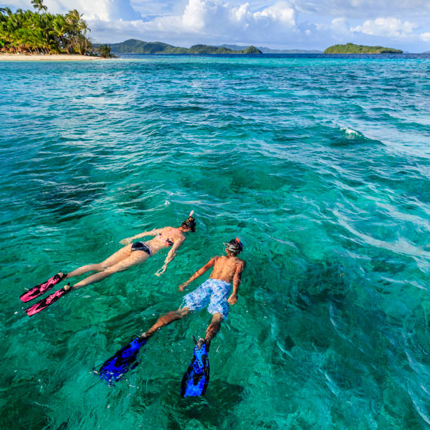 Young couple snorkeling on East China Sea, Philippines Young caucasian woman with her boyfriend snorkeling and watching turtles, East China Sea, Palawan Island, East China Sea, Philippines, Southeast Asia. snorkel stock pictures, royalty-free photos & images